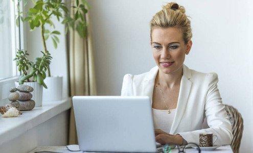 Junge Frau am Computer bereitet eine online Kreditanfrage bei Creditolo vor
