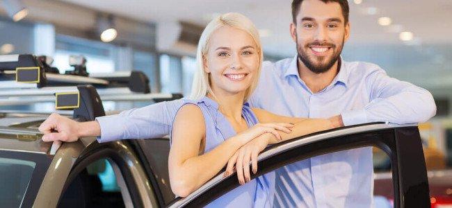 Ein zufrieden aussehendes Paar lehnt sich gegen die offene Tür ihres gerade erworbenen Neuwagens