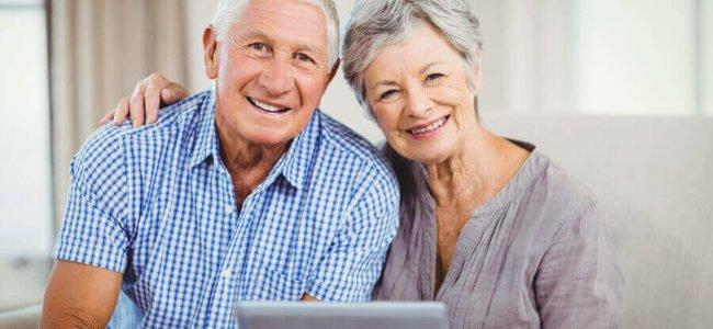 Glückliches Seniorenehepaar mit einem Tablet beantragt online ein Darlehen