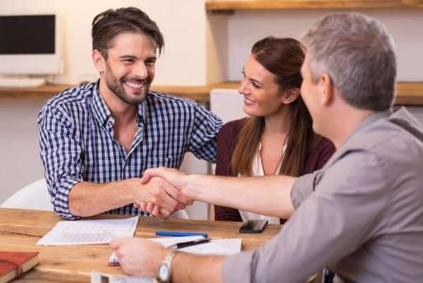 Kreditvermittler besiegelt einen günstigen Kreditabschluss mit einem jungen Ehepaar per Handschlag.