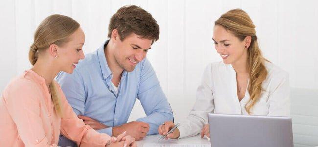 Ein junges Ehepaar lässt sich von einer Sachbearbeiterin der BBBank Kreditkonditionen erklären