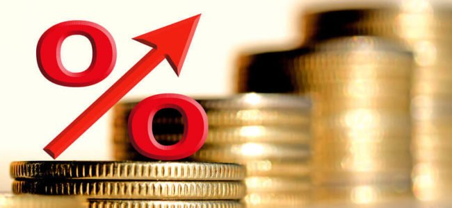 Rotes Zinssymbol und unterschiedlich hohe Münzstapel – Symbol für die Auswirkungen von Zinsmethoden