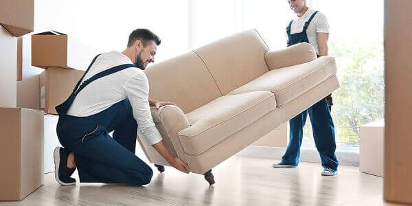 Mitarbeiter eines Umzugsunternehmens bringen ein Sofa in die neue Wohnung