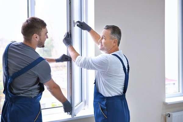 Auszubildender und Ausbilder setzen ein Fenster ein
