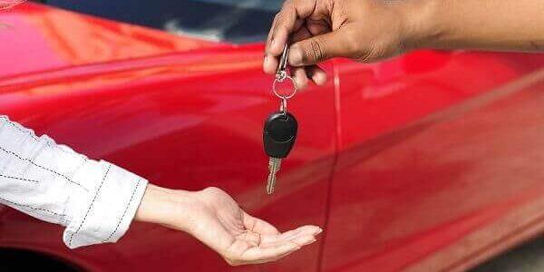Autohändler übergibt junger Frau Schlüssel nach Autokauf mit Absatzfinanzierung